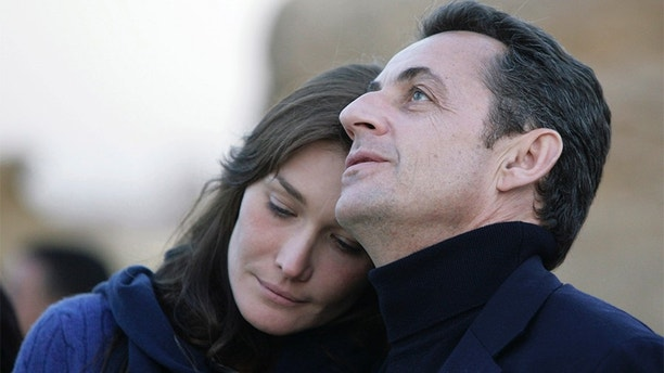 France's President Nicolas Sarkozy (L) and his new girlfriend, Carla Bruni, walk together during a visit to the Giza pyramids in Cairo, December 30, 2007. Singer and former super model Carla Bruni is living a true love story with French President Nicolas Sarkozy, her mother told a newspaper on Sunday.  REUTERS/Nasser Nuri (EGYPT) - GM1DWXVSWDAA