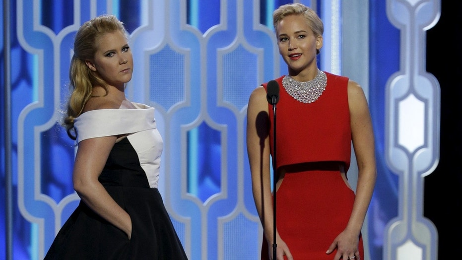 Amy Schumer (L) and Jennifer Lawrence presenting at the 73rd Golden Globe Awards in Beverly Hills, California January 10, 2016.