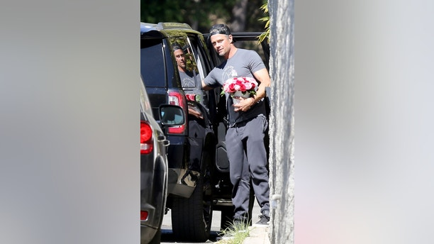 Josh Duhamel carries red and white flowers to Fergies home in Brentwood after her much ridiculed performance of the National Anthem. 