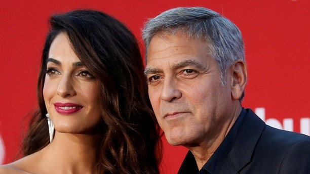 "FILE PHOTO: Director George Clooney and his wife Amal attend the premiere for ""Suburbicon"" in Los Angeles, California, U.S., October 22, 2017. REUTERS/Mario Anzuoni/File Photo - RC1F66B9B3A0"