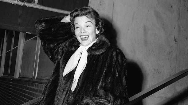 FILE - In this Dec. 10, 1955 file photo, actress Nanette Fabray poses as she leaves Mt. Sinai hospital in New York. Fabray, the vivacious, award-winning star of the stage, film and television, has died at age 97. Fabray's son, Dr. Jamie MacDougall, tells The Associated Press his mother died Thursday, Feb. 22, 2018, at her home in Palos Verdes Estates, Calif. (AP Photo/File)