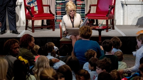 "Singer-songwriter Dolly Parton reads her book ""Coat of Many Colors,"" to children as she makes it the 100 millionth book that Imagination Library donates to the Library of Congress collection at the Library of Congress, Tuesday, Feb. 27, 2018 in Washington. The Library of Congress and Imagination Library also announce a story time for children on the last Friday of each month in the Great Hall of the Thomas Jefferson Building from March through August. (AP Photo/Andrew Harnik)"