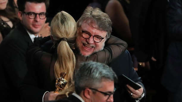 90th Academy Awards - Oscars Show – Hollywood - Director Guillermo del Toro is hugged by his guest Kim Morgan after winning Best Director for The Shape of Water. REUTERS/Lucas Jackson - HP1EE350C5F64