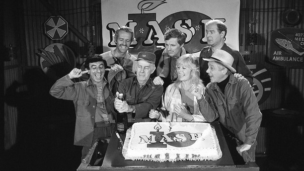 """FILE - In this Oct. 22, 1981, file photo, Jamie Farr, from front left, plugs his ears as cast members of the """"M.A.S.H."""" television series cast Harry Morgan, Loretta Swit, William Christopher and, from back from left, Mike Farrell, Alan Alda and David Ogden Stiers celebrate during a party on the set of the popular CBS program in Los Angeles. Stiers a prolific actor best known for playing a surgeon on the television series """"M.A.S.H."""" has died, the actor's agent Mitchell Stubbs confirmed Saturday night, March 4, 2018, in an email. He was 75. (AP Photo/Huynh, File)"""