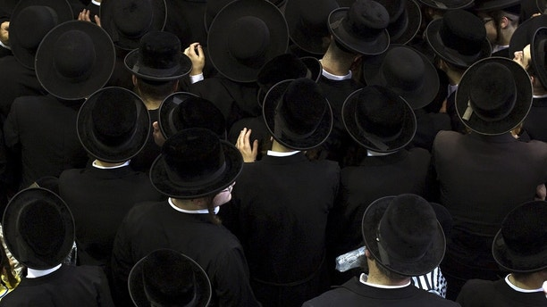Ultra-Orthodox Jewish men mourn the death of Rabbi Eliezer Hager of Viznitch during his funeral in Haifa, Israel July 8, 2015. Thousands of followers took part in the funeral of Hager, who was the leader of the Viznitch Hasidic movement in Haifa and died at the age of 91. REUTERS/Nir Elias       TPX IMAGES OF THE DAY      - GF10000152952