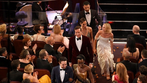Lin-Manuel Miranda, from left, Lupita Nyong'o lead other celebrities out of the Dolby Theatre at the Oscars on Sunday, March 4, 2018, in Los Angeles. The group visited a movie theater across the street to surprise movie-goers. (Photo by Chris Pizzello/Invision/AP)