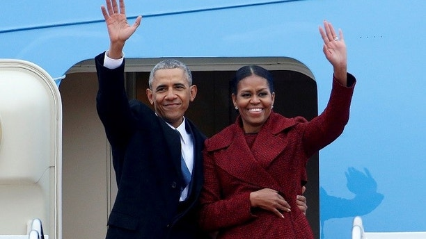 FILE PHOTO - Former President Barack Obama waves with his wife Michelle as they board Special Air Mission 28000, a Boeing 747 which serves as Air Force One, at Joint Base Andrews, Maryland, U.S. on January 20, 2017. REUTERS/Brendan McDermid/File Photo - RC15FF04B3F0