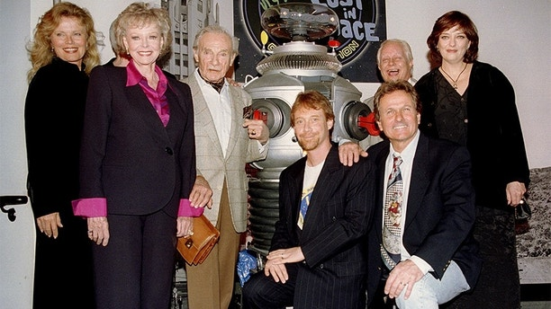 "The original cast members of the 1960s TV series ""Lost in Space"" pose during a reunion on the opening day of the movie ""Lost in Space,"" at the Hollywood Entertainment Museum on April 3. Left to right are Marta Kristen who played Judy Robinson, June Lockhart who played Maureen Robinson, Jonathon Harris who played Dr. Zachary Smith, Bill Mumy who played Will Robinson, Mark Goddard who played Major Don West, Dick Tufeld who played the robot, and Angela Carwright who played Penny Robinson. Several of the original characters appear in cameo performances in the newly released film.
