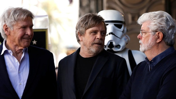 Actor Mark Hamill (C) talks with actor Harrison Ford (L) and filmmaker George Lucas after unveiling his star on the Hollywood Walk of Fame in Los Angeles, California, U.S., March 8, 2018. REUTERS/Mario Anzuoni - RC11CFEE6240