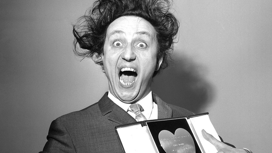 In this March 8, 1966 file photo, comedian Ken Dodd poses with his award for Show Business Personality of the Year, presented to him at the Variety Club's luncheon at the Savoy Hotel, London. British comedian Ken Dodd, whose seven-decade career stretched from the music-hall era to the age of social media, has died. He was 90.