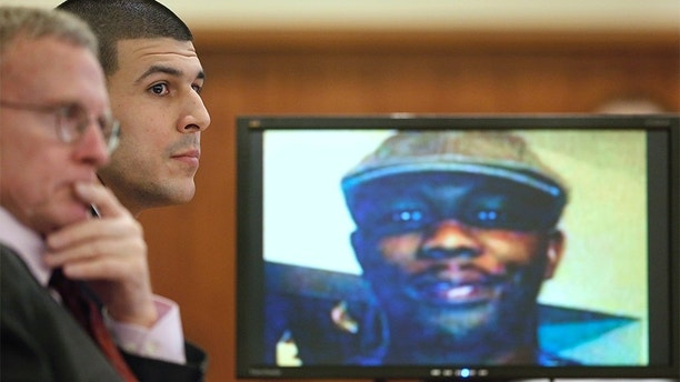 Former New England Patriots football player Aaron Hernandez listens during his trial as defense attorney Charles Rankin (L), looks on while an image of Odin Lloyd is displayed on a monitor in Fall River, Massachusetts, January 29, 2015. Hernandez is accused of murdering semi-professional football player Odin Lloyd. REUTERS/Steven Senne/Pool (UNITED STATES - Tags: CRIME LAW SPORT FOOTBALL) - TM3EB1T12JC01