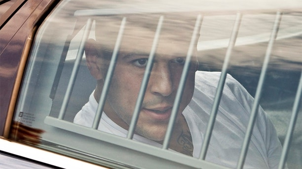New England Patriots tight end Aaron Hernandez is led out of the North Attleborough police station after being arrested June 26, 2013.  Hernandez, a 23-year-old rising football star with the New England Patriots, was arrested by police in a murder investigation and fired by the team on Wednesday, another blot on the National Football League's tightly protected image.  REUTERS/Dominick Reuter  (UNITED STATES - Tags: CRIME LAW SPORT FOOTBALL TPX IMAGES OF THE DAY) - GM1E96R06JJ01