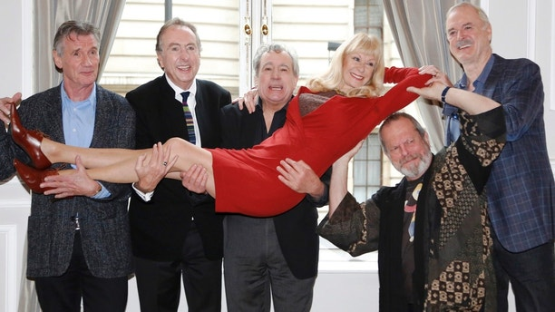The surviving members of the original cast of the Monty Python comedy team (L-R) Michael Palin, Eric Idle, Terry Jones,Terry Gilliam and John Cleese, hold Carol Cleveland as they pose for photographers at a photocall in central London November 21, 2013.    REUTERS/Luke MacGregor   (BRITAIN - Tags: ENTERTAINMENT SOCIETY) - LM1E9BL120K01