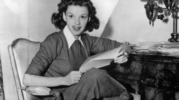 Judy Garland checking fanmail at her home.