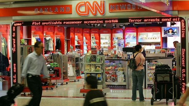 Passengers walk by the CNN store as headlines from a terror plot flash on a screen at the Oakland International Airport in Oakland, Calif., on Thursday, Aug. 10, 2006.  Travelers in the U.S. are facing heightened security at airports today after authorities in London uncovered a terror plot aimed at airlines traveling from Britain to the U.S. (AP Photo/Marcio Jose Sanchez)
