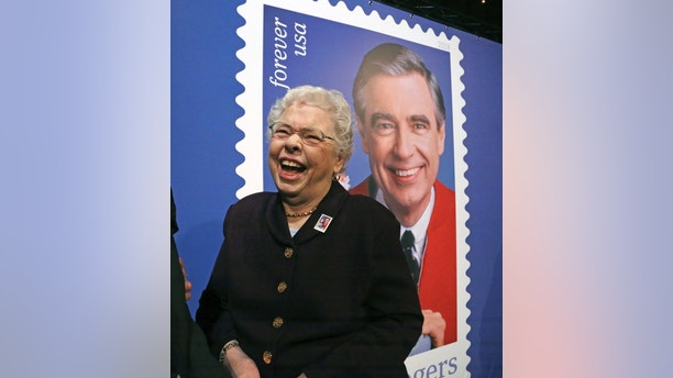 Fred Rogers wife, Joanne Rogers, shares a laugh with friends in front of a giant Mister Rogers Forever Stamp following the first-day-of-issue dedication in WQED's Fred Rogers Studio in Pittsburgh, Friday, March 23, 2018. (AP Photo/Gene J. Puskar)