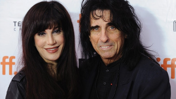 """Alice Cooper (R) and wife Sheryl Goddard pose on the red carpet before a screening of the film """"Supermensch: The Legend of Shep Gordon"""" at Roy Thomson Hall during the 38th Toronto International Film Festival in Toronto September 7, 2013."""