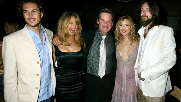 """Actress Kate Hudson poses with her family at the party following the premiere of her new comedy film """"Raising Helen"""" in Hollywood May 26, 2004. Shown (L-R) brother Oliver Hudson, Goldie Hawn, Hudson's mother,actor Kurt Russell,Hawn's companion,Kate Hudson and her husband, musician Chris Robinson.Hudson portrays a modeling agency assistant who suddenly is faced with the death of her sister and raising her sister's children. The film opens May 28 in the United States. REUTERS/Fred Prouser  FSP/JV - RTRKFRK"""
