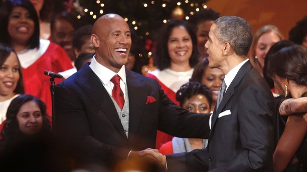 """U.S. President Barack Obama (R) greets actor Dwayne """"The Rock"""" Johnson (L) at the end of the taping of the 'Christmas in Washington' television special to benefit Children's National Medical Center in Washington December 14, 2014.   REUTERS/Jonathan Ernst    (UNITED STATES - Tags: POLITICS ENTERTAINMENT ANNIVERSARY) - GM1EACF0QVL01"""