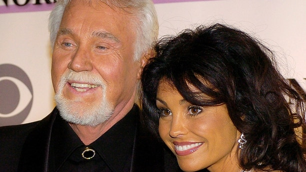 Country singer Kenny Rogers and his wife Wanda pose for photographers as the arrive at the Kennedy Center for the 29th Annual Gala in Washington December 3, 2006. This year's honorees are conductor Zubin Metha, theatre composer Andrew Lloyd Webber, singers Dolly Parton and Smokey Robinson and film director Steven Spielberg.   REUTERS/Mike Theiler (United States) - GM1DUBURWCAA