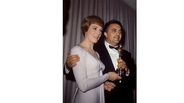 Fellini is shown in this 1964 picture as he is presented by actress Julie Andrews the 1964 Oscar for Best Foreign Film for his film 8-1/2 - PBEAHUNKFFA