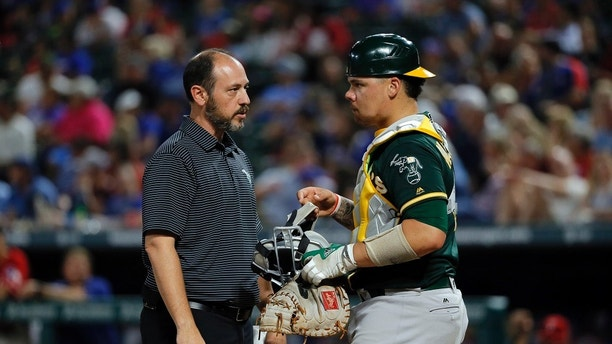 Oakland Athletics trainer Nick Paparesta, left, checks on catcher Bruce Maxwell after Maxwell was hit in the mask by a fouled ball off the bat of Texas Rangers' Ryan Rua in the fourth inning of a baseball game, Thursday, Sept. 28, 2017, in Arlington, Texas. (AP Photo/Tony Gutierrez)
