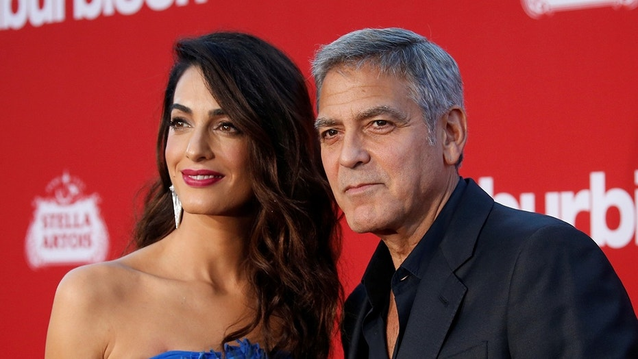 Director George Clooney and his wife Amal attend the premiere of