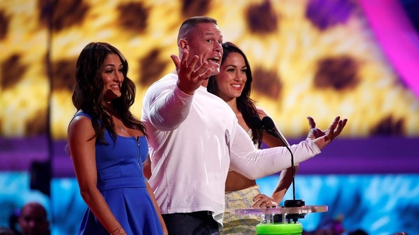 Wrestlers John Cena, Brie Bella and Nikki Bella (L) present the award for favorite male buttkicker at the 27th Annual Kids' Choice Awards in Los Angeles, California March 29, 2014.   REUTERS/Mario Anzuoni (UNITED STATES  - Tags: ENTERTAINMENT)  (KIDSCHOICE-SHOW) - TB3EA3U04GTPW