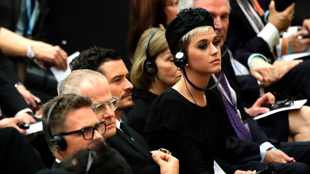 "Katy Perry, right, flanked by Orlando Bloom, center, attend an audience by Pope Francis for the participants in the ""United to Cure"" international conference on the cure for cancer in the Paul VI hall, at the Vatican, Saturday, April 28, 2018. (AP Photo/Alessandra Tarantino)"