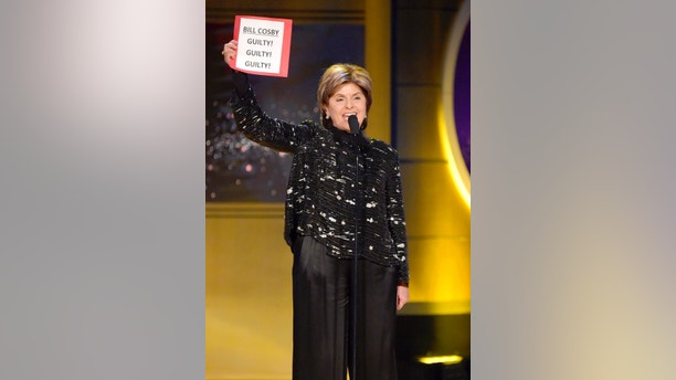 Gloria Allred carries a sign referencing the Bill Cosby verdict as she presents the award for outstanding legal/courtroom program at the 45th annual Daytime Emmy Awards at the Pasadena Civic Center on Sunday, April 29, 2018, in Pasadena, Calif. (Photo by Richard Shotwell/Invision/AP)