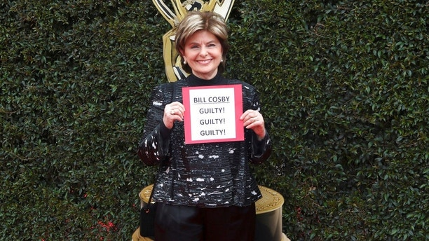 Gloria Allred carries a sign referencing the Bill Cosby verdict as she arrives at the 45th annual Daytime Emmy Awards at the Pasadena Civic Center on Sunday, April 29, 2018, in Pasadena, Calif. (Photo by Willy Sanjuan/Invision/AP)