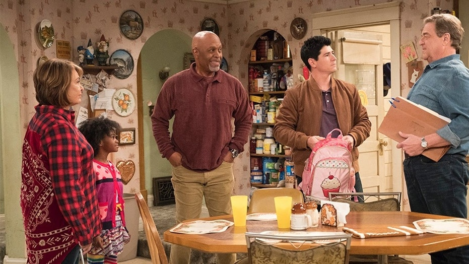 """Michael Fishman (holding pink backpack) during the episode """"Go Cubs"""" from the """"Roseanne"""" reboot."""