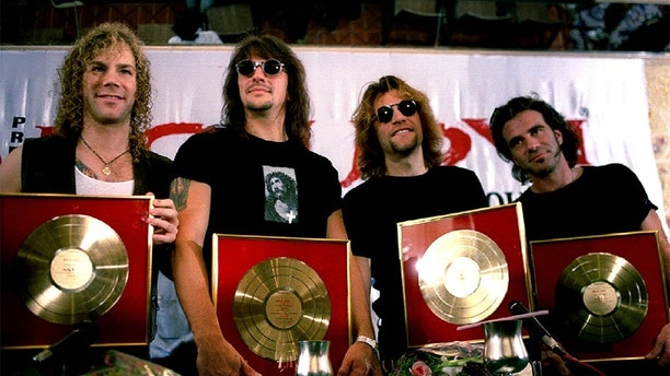 Members of the rock group Bon Jovi (L to R) David Bryan, Richie Sambora, Jon Bon Jovi and Tico Torres pose with golden discs presented to them by Polygram, one of India's largest music companies after their album registered record sales in Bombay. The group which addressed a press conference in the city on April 25 will perform at a sellout concert in aid of the National Association of the Blind tommorrow, April 26 - PBEAHUNAVCL