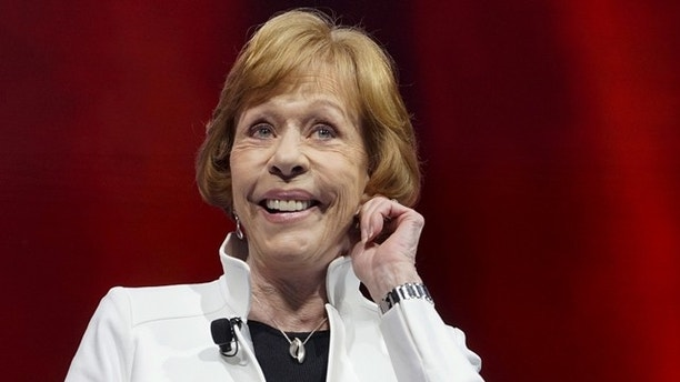 Actress Carol Burnett does her trademark ear tug at the annual meeting in Fayetteville, Arkansas June 5, 2015. Wal-Mart Stores Inc named Vice Chairman Greg Penner as its new chairman on Friday, replacing his father-in-law Rob Walton and cementing the founding family's influence over the board of the world's largest retailer.  REUTERS/Rick Wilking - RTX1FB5Y