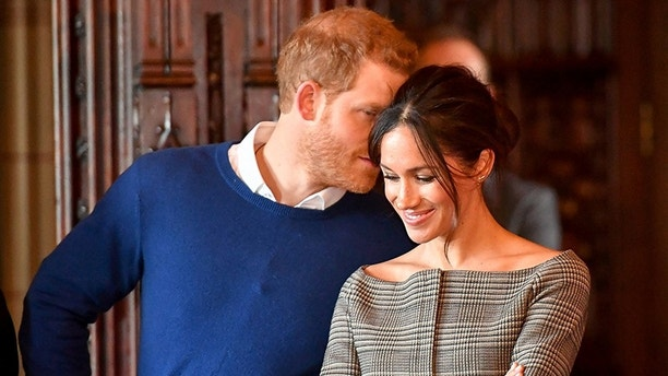 Britain's Prince Harry whispers to Meghan Markle as they watch a performance by a Welsh choir in the banqueting hall during a visit to Cardiff Castle in Cardiff, Britain, January 18, 2018. REUTERS/Ben Birchall/Pool - RC1A838B7CC0