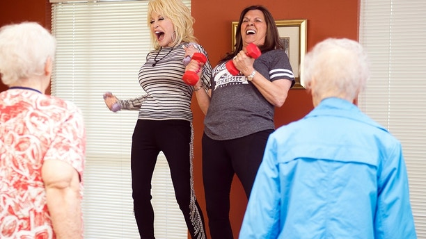 Country music superstar Dolly Parton, center left, joins in an exercise class at the renamed My People Senior Activity Center in Sevierville, Tenn., Monday, May 7, 2018. Parton came for a dedication ceremony Monday to rename the facility in honor of her parents, Robert and Avie Lee Parton. (Brianna Paciorka/Knoxville News Sentinel via AP)