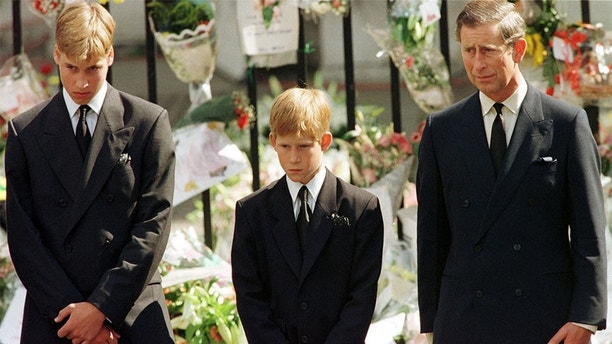 Prince Charles (R), Prince Harry (C) and Prince William look at the coffin of Diana, Princess of Wales, after it was placed into a hearse September 6. Hundreds of thousands of mourners lined the streets of Central London to watch the funeral procession. The Princess died last week in a car crash in Paris. - PBEAHUMOWCI