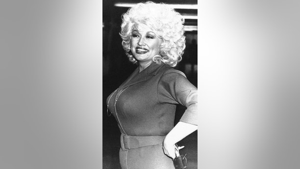 American country-western singing star Dolly Parton is greeted by fans as she returned to the Dominion Theatre in London on Tuesday, March 30, 1983  following the concert?s disruption by a telephoned bomb threat.   About 2,000 of the concertgoers streamed into the streets of London?s West End while police bomb experts searched the theatre but nothing was found. The concert resumed about an hour after it was halted. (AP Photo/Peter Kemp)