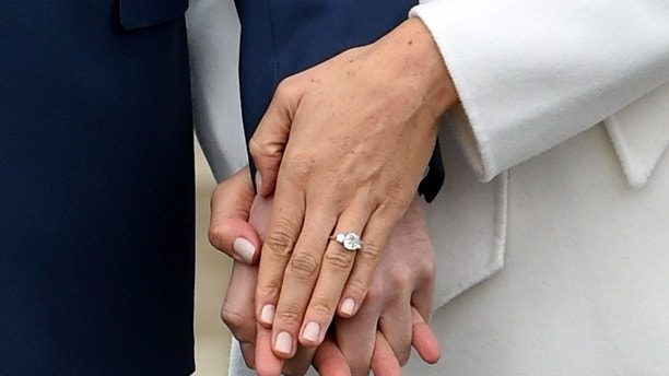Britain's Prince Harry poses with Meghan Markle, displaying her engagement ring, in the Sunken Garden of Kensington Palace, London, Britain, November 27, 2017. REUTERS/Eddie Mulholland/Pool - RC168FF77F90