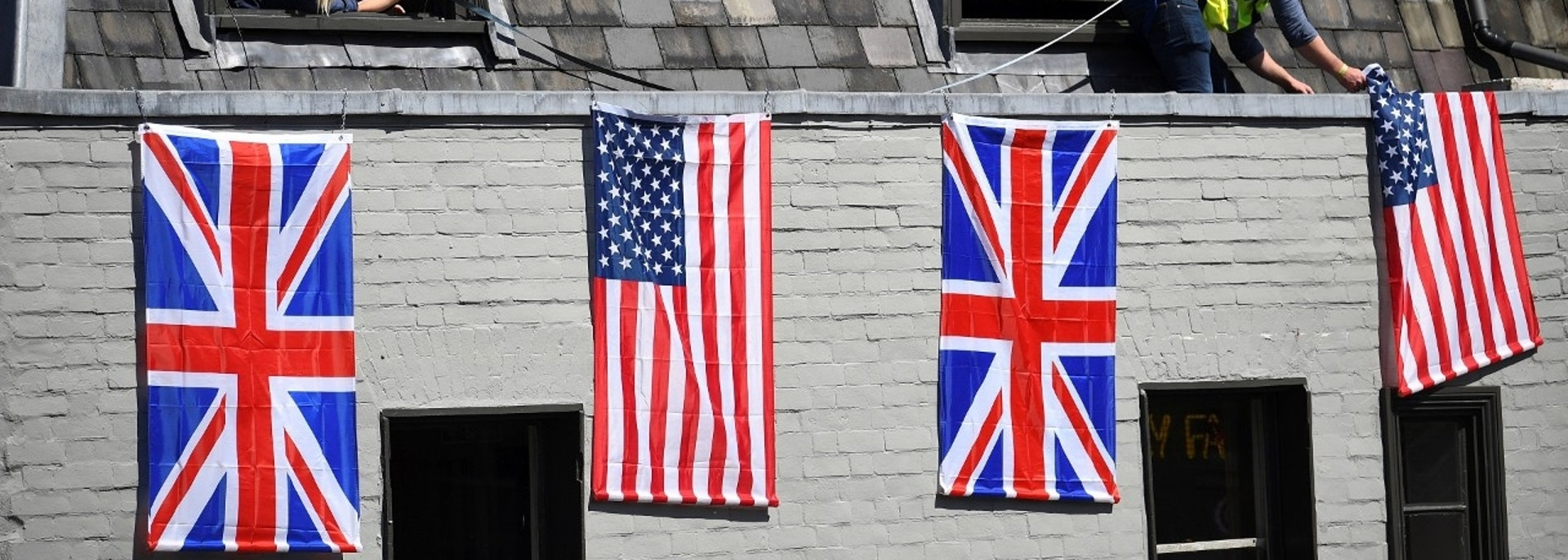 A man hangs U.S. and Union flags ahead of Britain's Prince Harry's wedding to Meghan Markle in Windsor, Britain, May 17, 2018. REUTERS/Dylan Martinez - RC129A020020