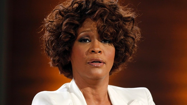 """Singer Whitney Houston looks on on the German TV game show """"Wetten Dass"""" (Bet it...?) in Freiburg October 3, 2009.  Wetten Dass is one of the most popular Saturday night programmes in Germany.  REUTERS/Johannes Eisele (GERMANY ENTERTAINMENT IMAGES OF THE DAY) - GM1E5A40MUK01"""