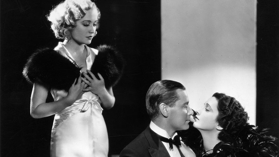 """Miriam Hopkins (left) looks on while Herbert Marshall and Kay Francis share a romantic moment during the filming of Paramount's 1932 romantic comedy, """"Trouble in Paradise"""", directed by Ernst Lubitsch."""