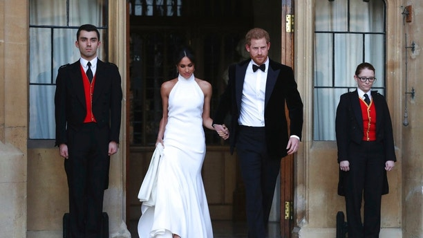 The newly married Duke and Duchess of Sussex, Meghan Markle and Prince Harry, leave Windsor Castle after their wedding in Windsor, England, to attend an evening reception at Frogmore House, hosted by the Prince of Wales, Saturday, May 19, 2018. (Steve Parsons/PA via AP)