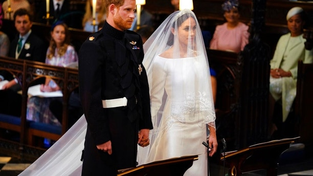 Britain's Prince Harry and Meghan Markle stand, prior to the start of their wedding ceremony, at St. George's Chapel in Windsor Castle in Windsor, near London, England, Saturday, May 19, 2018. (Dominic Lipinski/pool photo via AP)