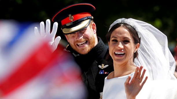 Britainís Prince Harry and his wife Meghan wave as they ride a horse-drawn carriage after their wedding ceremony at St Georgeís Chapel in Windsor Castle in Windsor, Britain, May 19, 2018. REUTERS/Damir Sagolj     TPX IMAGES OF THE DAY - RC1BFBB1C9A0