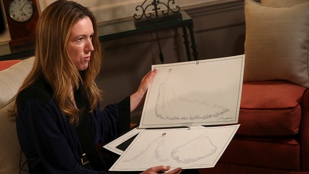 Clare Waight Keller, designer at Givenchy, holds sketches as she gives an interview the day after Meghan Markle walked down the aisle of St George's Chapel in Windsor and married Prince Harry wearing the dress that she created, in Kensington Palace, London, Britain, May 20, 2018. REUTERS/Hannah McKay/Pool  FOR EDITORIAL USE ONLY. NO RESALES. NO ARCHIVES - RC13337DF0E0