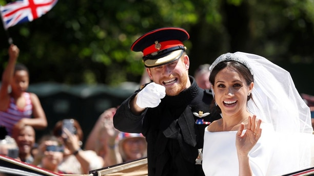 Britain's Prince Harry and his wife Meghan wave as they ride a horse-drawn carriage after their wedding ceremony at St George's Chapel in Windsor Castle in Windsor, Britain, May 19, 2018. REUTERS/Damir Sagolj - RC1E8A85A630