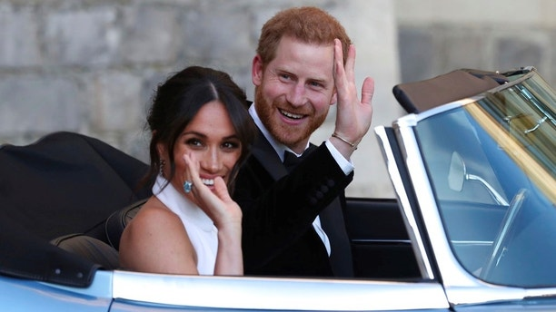 The newly married Duke and Duchess of Sussex, Meghan Markle and Prince Harry, leave Windsor Castle in a convertible car after their wedding in Windsor, England, to attend an evening reception at Frogmore House, hosted by the Prince of Wales, Saturday, May 19, 2018. (Steve Parsons/pool photo via AP)