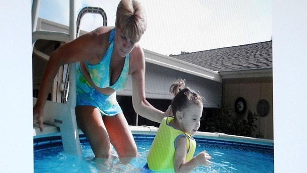An image projected on a courtroom monitor shows Cindy Anthony (L) with her granddaughter Caylee, in a swimming pool which was submitted as evidence in the Casey Anthony trial at the Orange County Courthouse in Orlando, Florida June 24, 2011.    REUTERS/Red Huber/Pool   (UNITED STATES - Tags: CRIME LAW) - GM1E76P06YY01