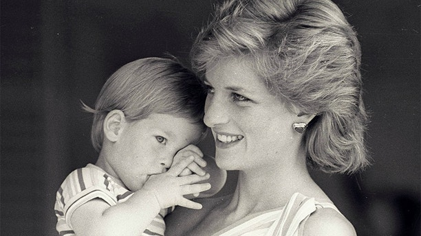 Young Prince Harry tries to hide behind his mother Princess Diana during a morning picture session at Marivent Palace on August 9, 1988, where the Prince and Princess of Wales are holidaying as guests of King Juan Carlos and Queen Sofia.    REUTERS/Hugh Peralta - GF2DUBFABYAF